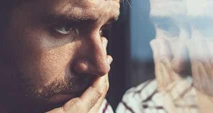 Trennung verarbeiten: Mann schaut nachdenklich aus dem Fenster