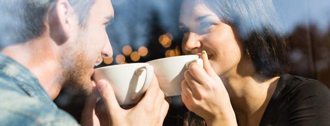 Mann und Frau halten Blickkontakt mit Kaffee in der Hand
