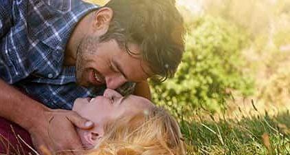 Frau erobern: Mann liegt mit Frau auf dem Boden und will sie küssen
