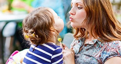 Partnersuche mit Kind: Mutter küsst Kind