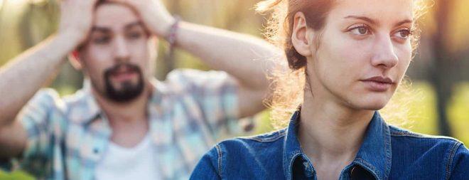 Trennung trotz Liebe: Frau im Vordergrund schaut weg und Mann im Hintergrund ist verzweifelt
