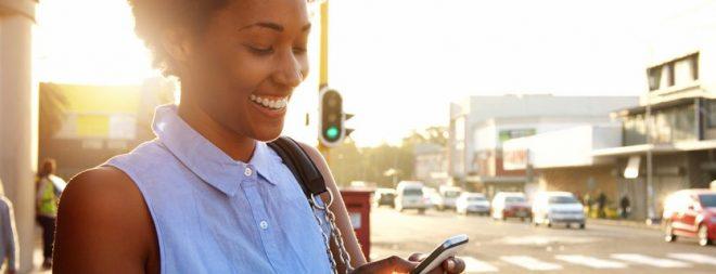 Mingle: Frau auf der Straße schaut auf Handy