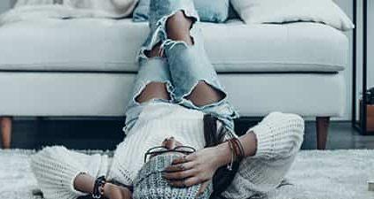 Ex vergessen: Frau liegt auf dem Boden mit Beinen auf dem Sofa