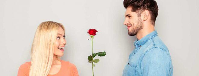 Mann hat ein Kompliment für eine Frau und schenkt ihr eine Rose.