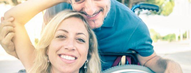 Partnersuche mit Handicap: Mann im Rollstuhl zusammen mit seiner Partnerin beim Selfie machen.