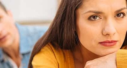 Mann und Frau stehen unglücklich nebeneinander weil die Beziehung durch einen Trennungsgrund kaputt gegangen ist