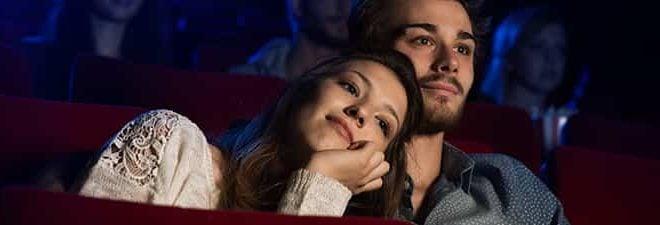 Frau lehnt an Schulter des Mannes beim Date im Kino.