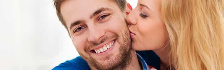 Frau macht ein Kompiment für einen Mann und gibt ihn einen Kuss auf die Backe.