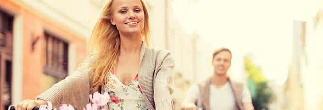 Frau glücklich auf dem Rad, weil Sie Mann auf einem Flirtportal kennengelernt hat.
