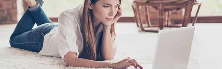 Frau mit sitzt mit ihrem Tablet auf der Couch und testet Singlebörse