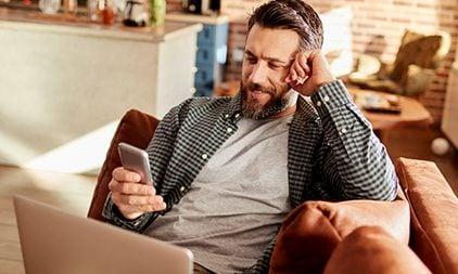 Ein Mann guckt auf sein Handy und lacht