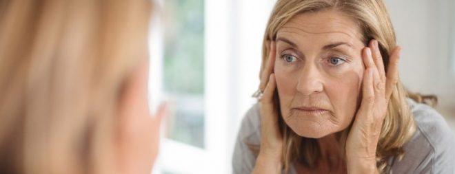 Midlife Crisis - Frau schaut nachdenklich im Spiegel