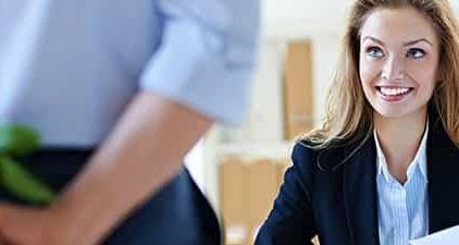 Flirten am Arbeitsplatz - Mann schenkt Frau Blumen