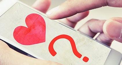 Fragen zum Verlieben - Handy mit Fragezeichen und Herz im Display