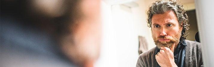 Midlife Crisis - Mann schaut nachdenklich im Spiegel