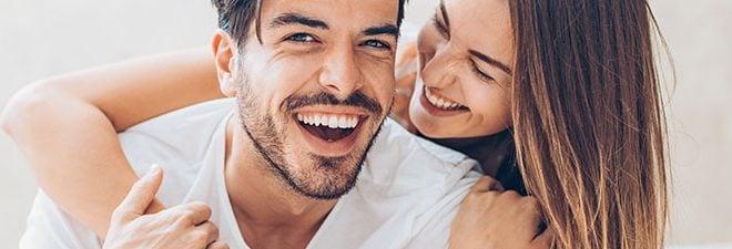 Mann und Frau lächeln sich an, als Zeichen für eine glückliche Beziehung