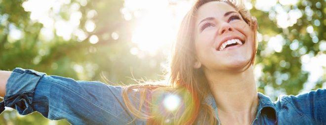 Frau strahlt und streckt die Hände in die Luft - sie ist glücklicher Single
