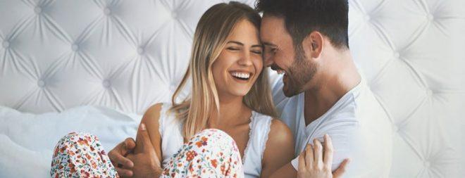 Rosarote Brille: Mann und Frau sind verliebt und frühstücken im Bett