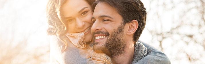 """Glückliche Frau umarmt mann als Antwort auf die Frage:""""Passen wir zusammen?"""""""