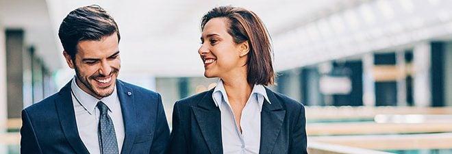 Frau lächelt Mann im Anzug an - sie ist verliebt in den Chef
