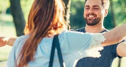 Frau und Mann laufen zur Begrüßung beim ersten Date mit offenen Armen auf sich zu.