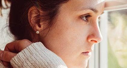 Frau ist verliebt in vergebenen Mann und steht zweifelnd am Fenster