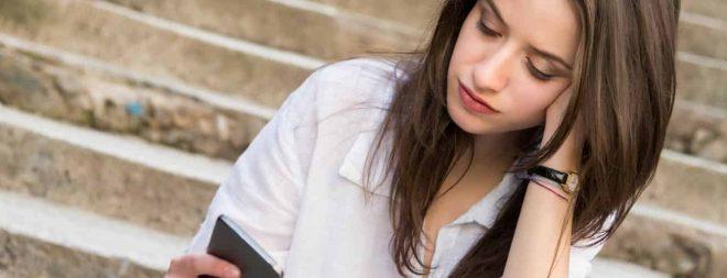 Eifersüchtig auf Ex: Frau schaut nachdenklich auf das Handy