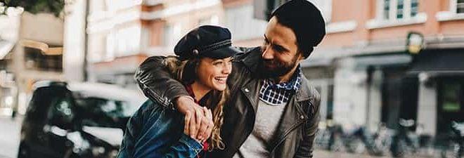 Mann lächelt und umarmt Frau - er kann Frauen zum lachen bringen