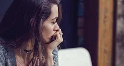 Frau schaut nachdenklich aus dem Fenster aufgrund von Verlustangst