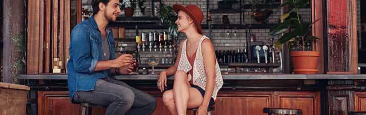 Frau an der Bar mit Mann - will Männer kennenlernen