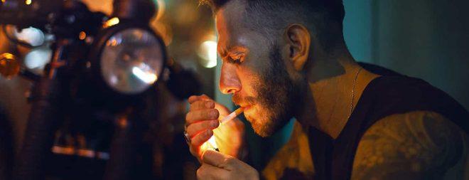 Er zieht sich zurück: Mann sitzt im dunkeln am Gehsteig und zündet sich Zigarette an.