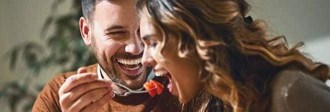 Mann versucht eine Frau zu verführen, indem er sie mit Schokofrucht füttert