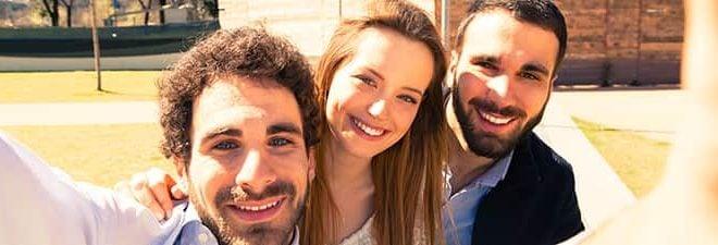 Frau macht Mann eifersüchtig, indem Sieein Selfie mit zwei anderen Männern macht