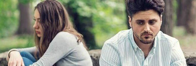 Mann und Frau mit Zweifel an der Beziehung voneinander abgewandt auf einer Parkbank