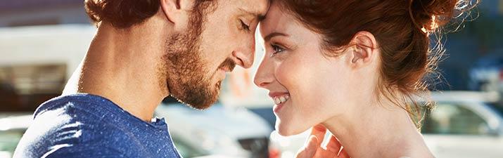 Mann und Frau haben Schmetterlinge im Bauch und stehen Stirn an Stirn gelehnt gegenüber
