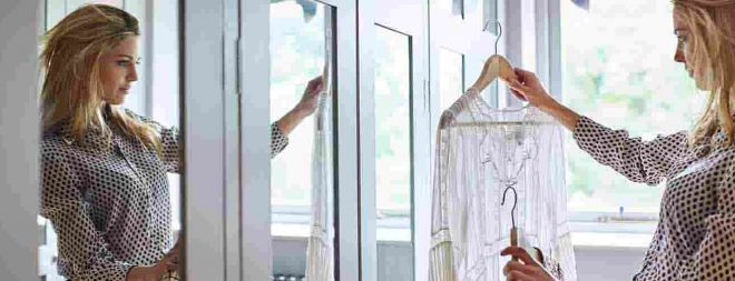 """Frau fragt sich """"Wie mache ich mich interessant?"""" und steht mit einer weißen Bluse in der Hand fragend vor dem Kleiderschrank"""
