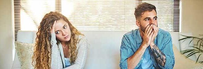 Paar steht vor dem Beziehungsende und sitzt ratlos nebeneinander auf der Couch